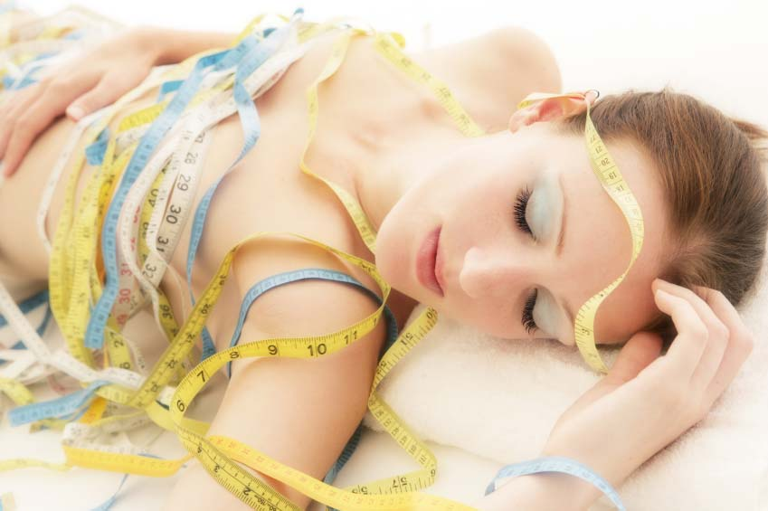 Woman Asleep Wrapped in Measuring Tapes