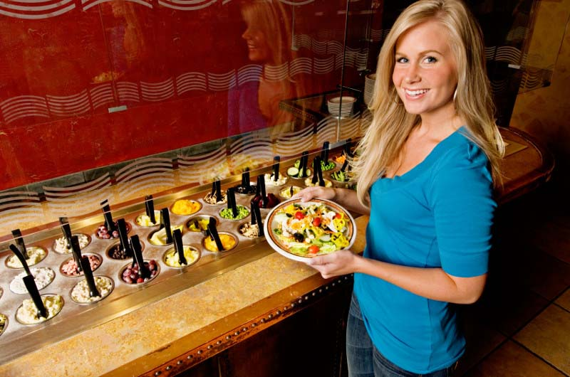 Woman Fixing a Plate at American Salad Bar
