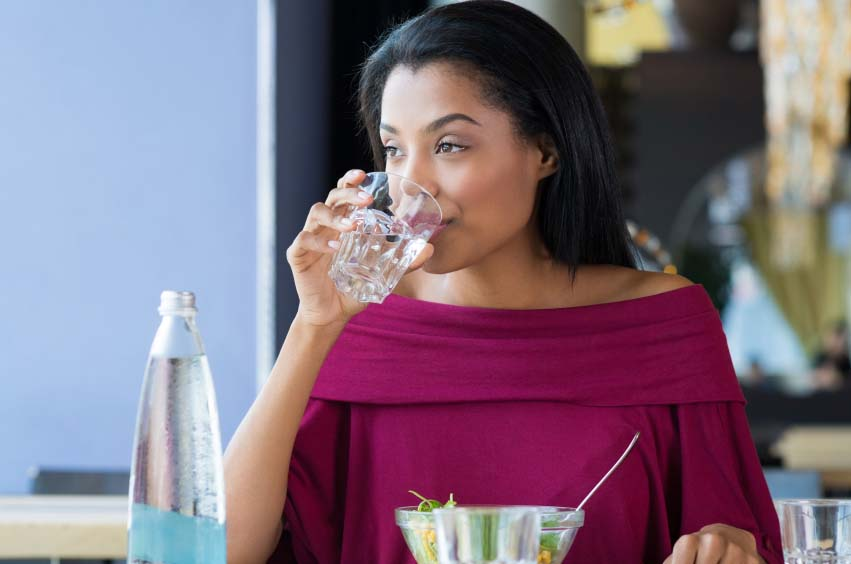 Woman Quenching Hunger with Glass of Water
