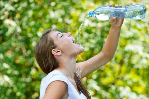 Woman Pouring Water into Mouth