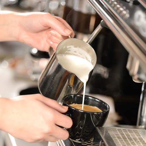 Barista Pouring Cream Into Cup of Coffee