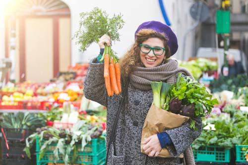 Woman Holding Fresh Carrots at Farmers Market