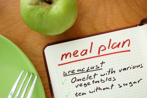 Open Meal Plan Book with Green Apple