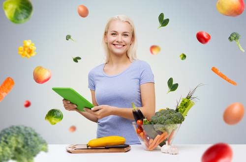 Woman in Kitchen Juggling Fresh Vegetables