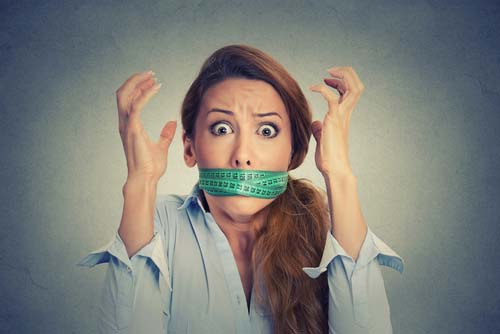 Stressed Woman with Measure Tape Wrapped Around Her Mouth