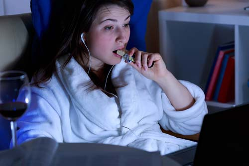 Woman Late Night Snacking in Front of Computer