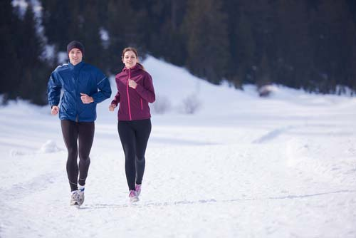 Couple Jogging on Snow-Covered Road