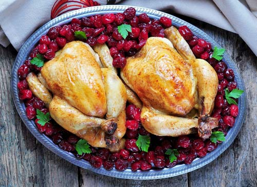 Two Roasted Chickens Surrounded by Cooked Cranberries