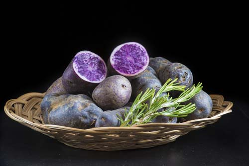 Basket with Whole and Cut Purple Potatoes