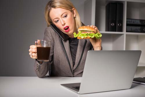 Woman at Desk Eating Fast Food