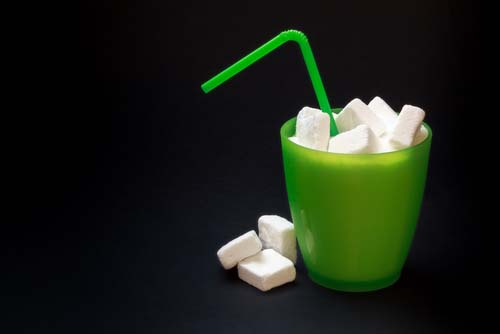 Straw Sticking Out of Plastic Cup Full of Sugar Cubes