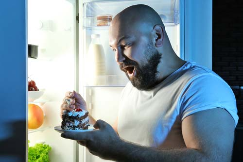 Man Eating Late Night Treat in Refrigerator Door